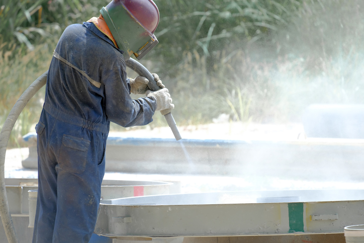 Worker is remove paint by air pressure sand blasting in a field, And wear a suit for protection